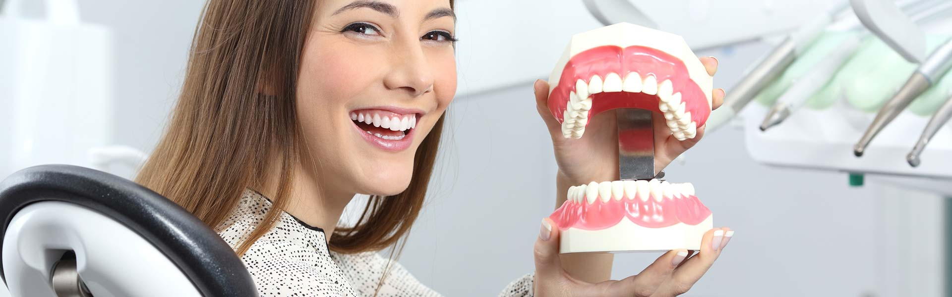 Smiling girl holding model of dentures