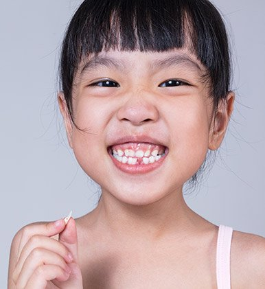 Little girl with tooth in her hand