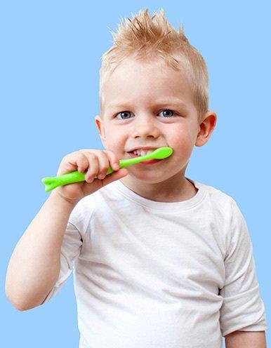 Boy smiling while brushing his teeth