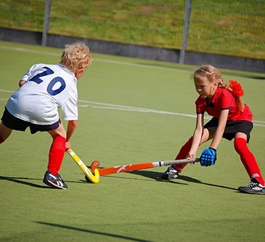 Children playing hockey wearing mouth guards